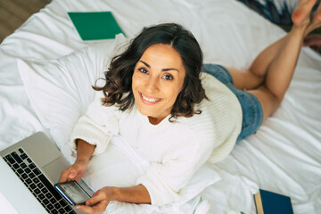 Happy beautiful young brunette woman is working with her laptop while she lay in bed at home. The freelance girl is surfing on internet