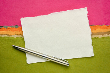 small sheet of blank white Khadi rag paper from South India with a metal pen against colorful abstract landscape