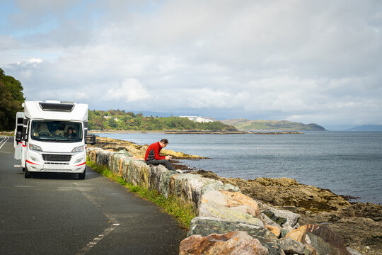 Summer family vacation in a motorhome. Male driver taking a break and looking at a mobile phone at a parking place by a sea. Female passanger in a car