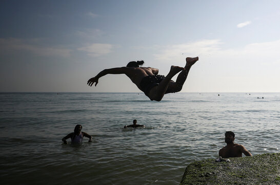 A man jumps into water during hot weather at Brighton beach