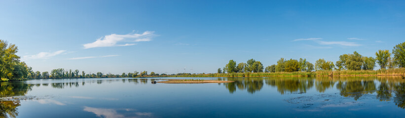 Photo sur Plexiglas Europe de l Est Panoramic view over a lake near Elbe river with wind turbines at sunny day and blue sky, Magdeburg, Germany..