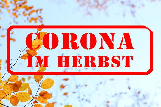 Roter Stempel mit Schriftzug: Corona im Herbst, ist im Herbst, als Warnung, auf blauem Himmel, vor Ast mit schönem gelben und orangen Herbslaub, gestempelt III.