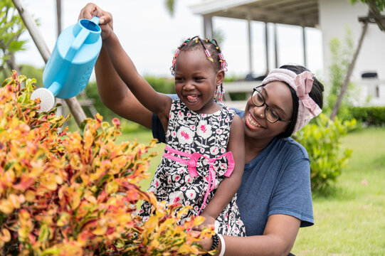 smile african girl help mother water the plants at outdoor her home garden. - happy family lifestyle concept.