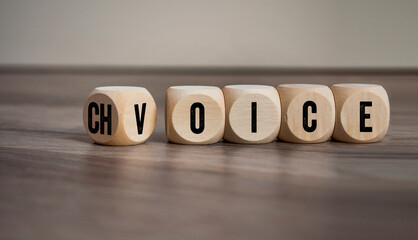 Cubes and dice with choice and voice on wooden background