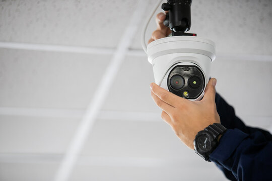 Technician installing IP wireless CCTV camera by screwed for home security system and installed
