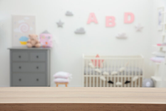 Empty wooden table in baby room. Space for text