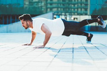 Strong Caucasian sportsman with muscular body shape doing push ups on street enjoying morning workout, strength male athlete in electronic headphones keeping vitality and wellness on activity