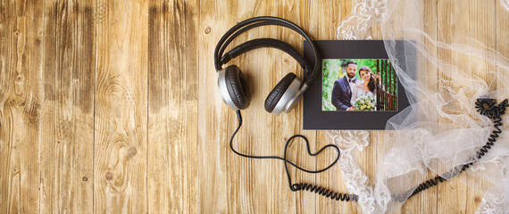 wooden background - beautiful picture of bride and groom and headphones