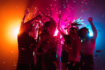 Confetti. A crowd of people in silhouette raises their hands, dancing on dancefloor on neon light background. Night life, club, music, dance, motion, youth. Bright colors and moving girls and boys.
