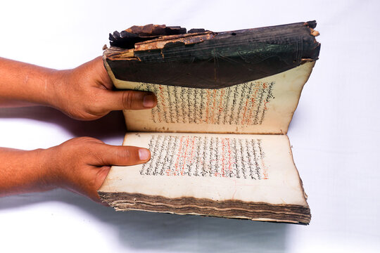 hands holding an antique Arabic script book with worn leather cover on white background