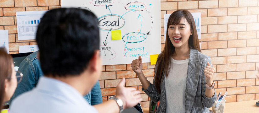Banner or header of happy beautiful young asian businesswoman excited with win reward from boss in small meeting in corporate workforce reskill upskill concept. Joyful promote staff or employee.