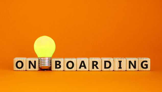 Wooden cubes with word 'onboarding'. Yellow light bulb. Beautiful orange background. Business concept. Copy space.