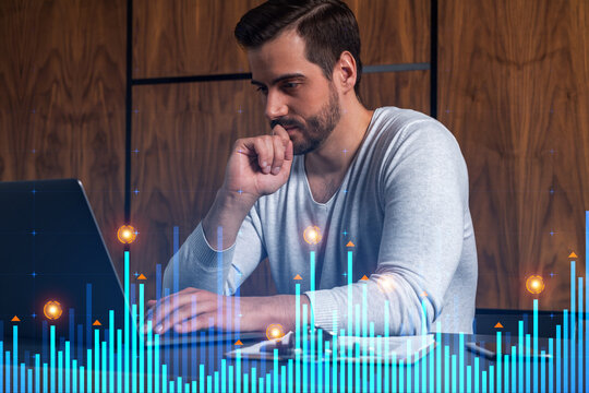 A serious caucasian analyst in casual wears, using laptop to proceed the forecast of behavioral statistic information. Double exposure. Graph Hologram. Concept of analytics in consulting.