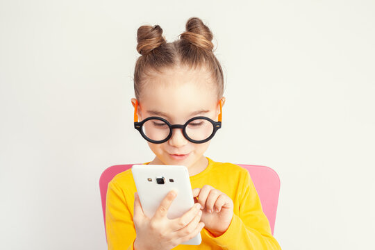 Beautiful cute little girl with eyeglasses holding smartphone in her hand and making gesture on screen. Child from alpha generation playing or using mobile app or playing game on smartphone. .