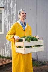 Cheerful young man carrying vegetable harvest on farm