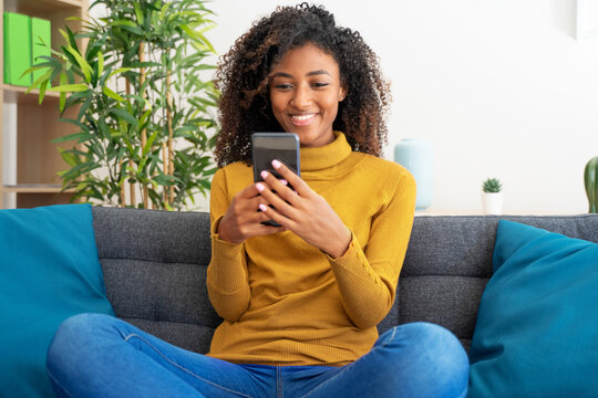 Confident black woman scrolling on smartphone at home