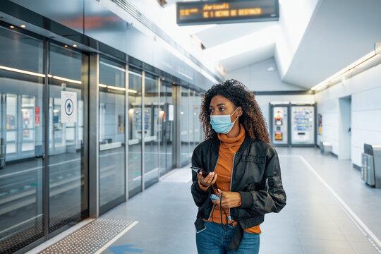 Black woman traveling on public transport and wearing face mask during coronavirus pandemic