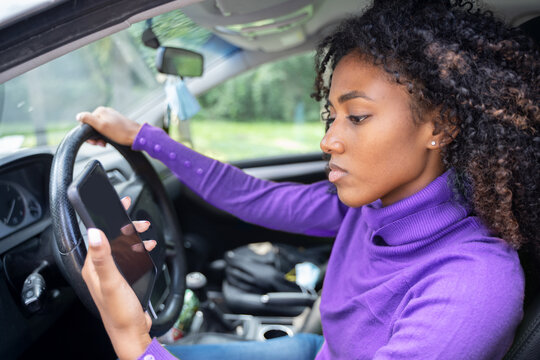 Young woman driving car and texting on her smart phone