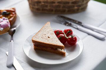 Plate with delicious sandwich and fresh tomatoes