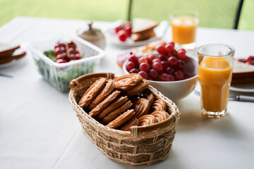 Tasty cookies, fruits and orange juice on white table
