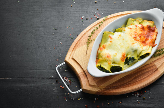 Cannelloni paste baked with spinach, cream sauce, cheese. Italian cuisine. Top view. Free copy space.