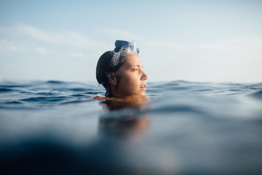 A Portrait Of A Woman In The Ocean With Goggles Looking Into The Distance
