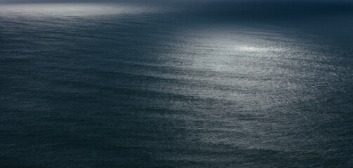 View of dappled sunlight on ocean waves and surf at dusk