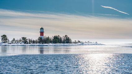 Very close view of red white lighthouse in middle of frozen, snowed island at cold Baltic Sea, partly open water, thin ice reflecting day light. Blue sky, light breeze. Northern Sweden, Umea