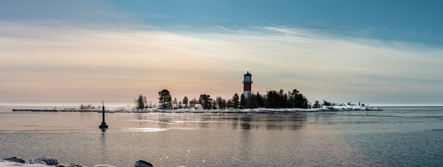 Panorama of red white lighthouse in middle of frozen, covered with snow island at cold Baltic Sea, partly open water, thin ice reflecting daylight. Blue sky, light breeze. Northern Sweden, Umea