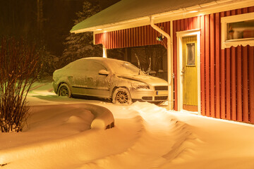 Silver colored car covered with much fresh snow afer snowfall. Parking is close to red wooden garage, typical Swedish architecture style. Night time, automobile is illuminated by strong light, trees.