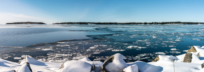 Panorama of winter coast at Baltic Ses, open water, floating ice, fresh snow covers big stones at coast line, blue sky, sunny day, light breeze, islands with pine tree forest. Northern Sweden, Umea