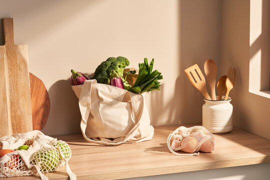 Cotton bags with groceries near wooden utensils in kitchen
