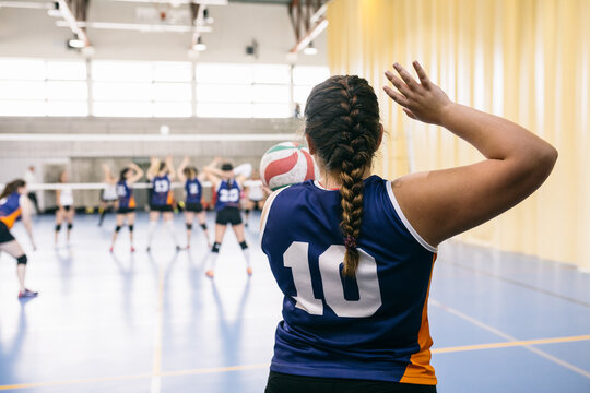 Competitive female volleyball player serving ball while tournament in Madrid, Spain.