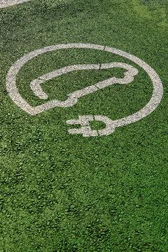 Electric car parking and charging station sign on asphalt