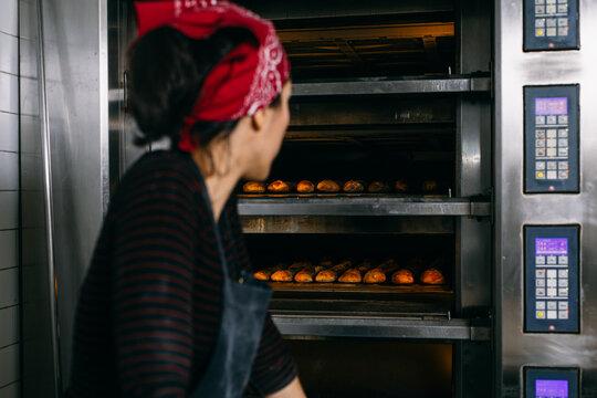 Baker checking bread in oven