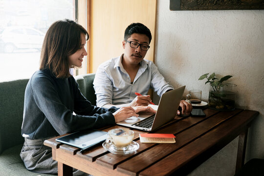 Caucasian woman and asian man coworking