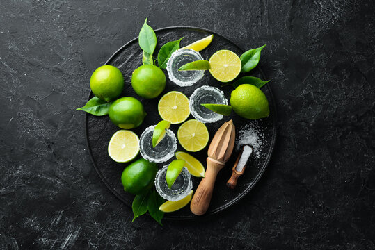 Tequila salt and lime. Alcohol. On a black stone background. Top view. Free space for your text.