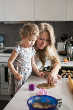 Little girl baking cookies with her mom