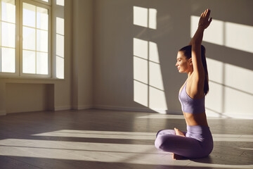 Girl woman yoga in lotus position relaxes in the morning at sunrise in classroom. .