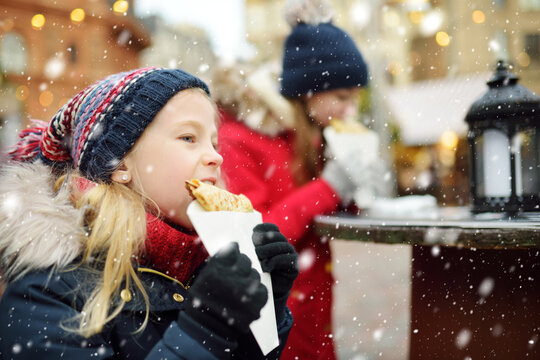 Cute young girls eating crepe pancake on traditional Christmas fair in Vilnius, Lithuania. Children enjoying sweets, candies and gingerbread on Xmas market.
