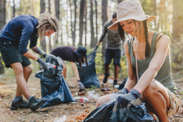 Young woman with group of activists cleaning forest of debri folding and plastic in bag