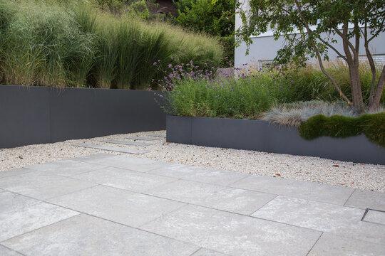 Moderne Garten- und Terrassengestaltung im Materialmix: Flachdach Garten Terrasse aus Naturstein Platten umgeben von Schotter und Metallkübeln mit Grünpflanzen und Ziergräsern im Herbst