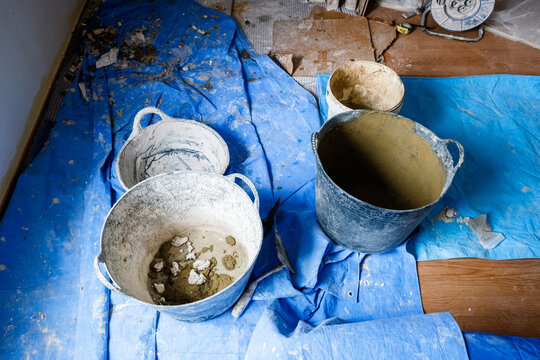 Dirty buckets and used with cement by bricklayers during a botched house.