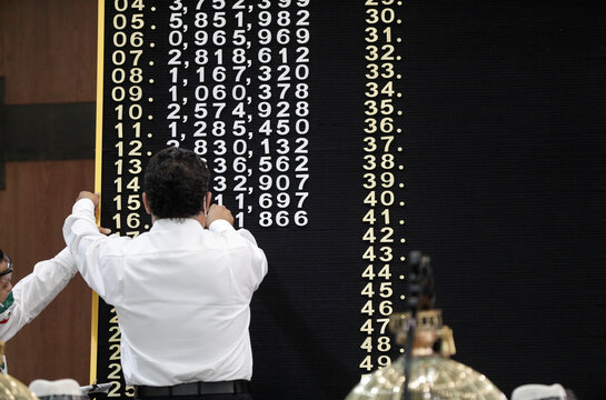 A man puts winning numbers on the board during a lottery raffle for the value of the last president's luxury plane at the National Lottery building in Mexico City