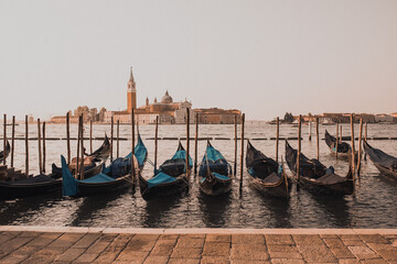 wooden gondolas stand tied in water near the central square of Venice. Chiesa di San Giorgio Maggiore. background