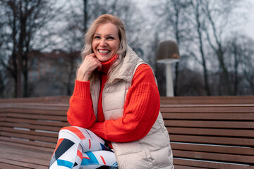 Mature Blonde Woman Smiling And Sitting On Bench In Modern Park After Active Exercising Outdoors. Lifestyle Of Senior Aged People. Sport And Relaxation After Park Run AT Mid Age