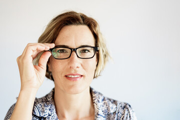 Real mature, active and modern woman, putting on her clear prescription glasses