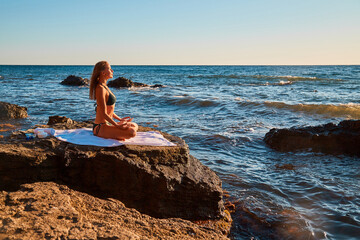 Woman meditating in lotus position. Female enjoying ocean view sitting on rock. Yoga and pilates concept, copy space