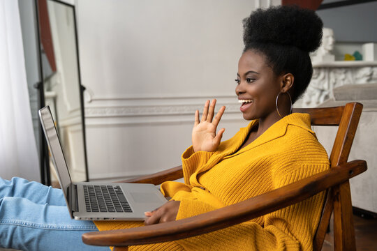 Smiling African American biracial millennial woman with afro hairstyle in yellow cardigan resting, sitting on armchair, talking in video chat with her friends, say hello.