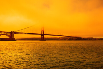 Wildfires smoky orange sky on Golden Gate bridge of San Francisco skyline from Fort point. Californian fires in United States of America. Composition about wildfires and climate change concept.